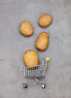 Ziemniaki i supermarket wózek na stole.