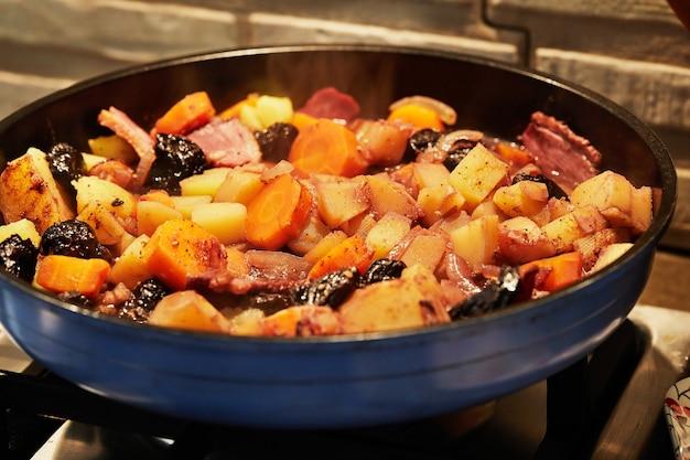 Ziemniaki, marchewki, szynkę i czarny czosnek smaży się na patelni.