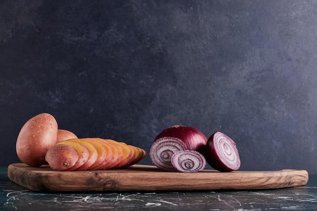 Ziemniaki na drewnianej desce z cebulą na boku.