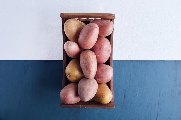 Ziemniaki na drewnianej tacy.