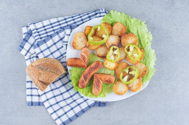 Ziemniaki smażone z kiełbasami pokrojone w plastry i smażone na oleju, i.