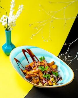 Ziemniaki smażone z krążkami czerwonej cebuli marynowane ogórki i skropione sosem