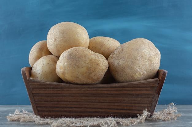 Ziemniaki w pudełku, na ręczniku, na marmurowym stole.