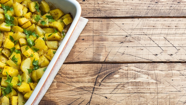 Ziemniaki zapiekane z przyprawami i ziołami na ceramicznej blasze do pieczenia. kuchnia wegetariańska. copyspace