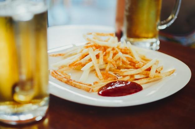 Ziemniaki ze złotymi frytkami gotowe do spożycia z ketchupem w czerwonym sosie i piwem