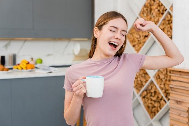 Ziewająca kobieta trzyma filiżankę w kuchni