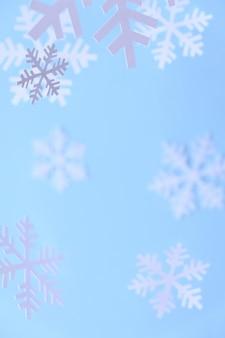 Zima białe płatki śniegu wycięte z białego papieru na niebieskim tle.