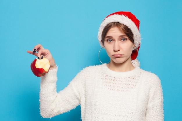 Zima, boże narodzenie, ludzie, koncepcja piękna - ładna blond nosi świąteczny kapelusz na jasnoniebieskim tle. portret młodej pięknej ślicznej wesołej dziewczyny uśmiechający się patrząc na kamery na białym tle.