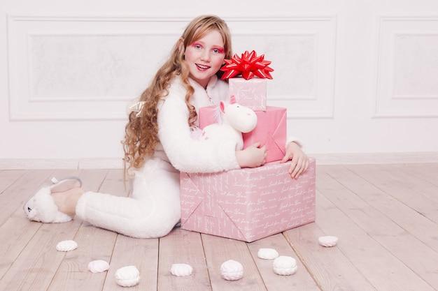 Zima, boże narodzenie, wakacje, słodycze, urodziny, uroczystości i koncepcja dzieci - cute little girl piżamy ze słodyczami siedzącymi na podłodze, koncepcja szczęśliwego dzieciństwa. prezenty dla dziewczynki, miękki pies, bańki mydlane.