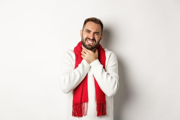 Zima, covid-19 i koncepcja zdrowia. chory mężczyzna skarży się na ból gardła, dotyka szyi i krzywi się z bólu, stoi w swetrze i czerwonym szaliku, białe tło