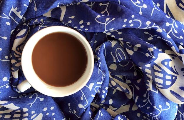 Zima filiżanka kawy z szalikiem w tle. ponad światłem