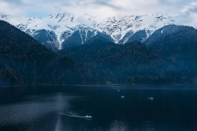 Zima jezioro ritsa w abchazji z górami w śniegu w tle, późnym wieczorem.