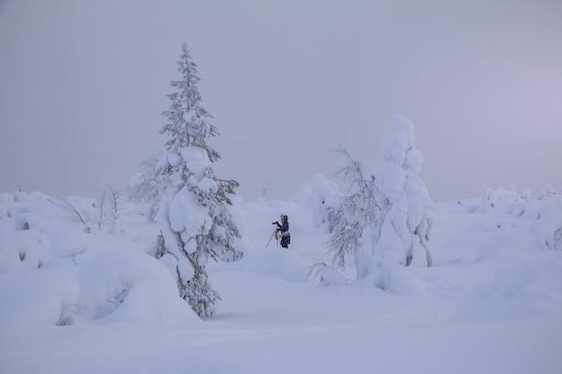 Zima na północy finlandii. dużo śniegu i obfite opady śniegu. kobieta fotograf strzela ze statywu