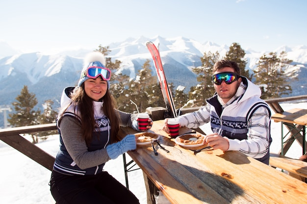 Zima, narty - narciarze jedzący lunch w zimowych górach.