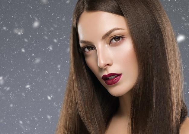 Zima piękna brunetka kobieta czerwone usta manicure z długimi włosami naturalny makijaż twarzy zbliżenie. strzał studio. kolor tła.