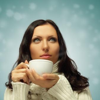 Zima - piękna kobieta przy gorącej kawie lub herbacie