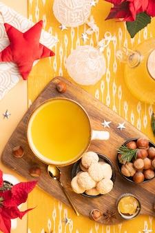 Zima płasko z herbatą imbirową, ciasteczkami, orzechami i świątecznymi dekoracjami na stole