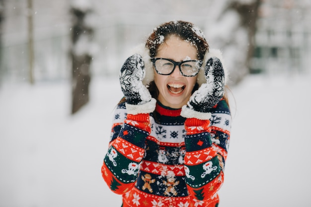 Zima portret młoda piękna dziewczyna jest ubranym nauszników, pulower pozuje w śnieżnym parku. kobieta szuka i uśmiecha się