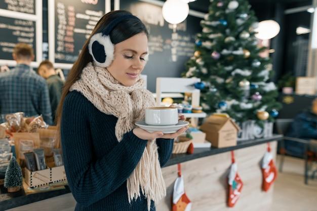 Zima portret młodej pięknej kobiety w szalik z dzianiny, futro uszy, ciepły sweter z filiżanką kawy
