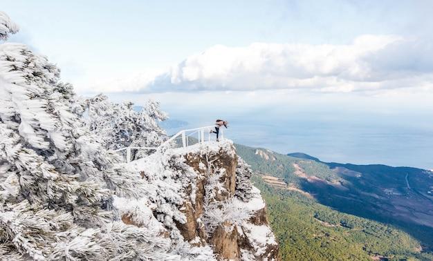 Zima portret yong dziewczyna przy śnieżnym lasem. śnieżny lanscape na szczycie góry