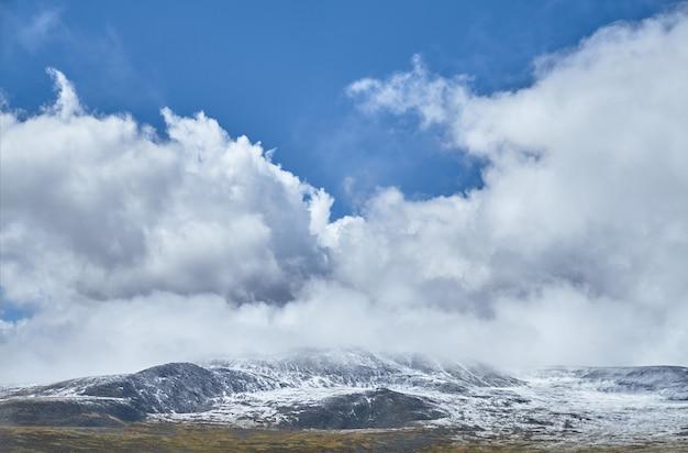 Zima przyszła na step syberyjski, ośnieżone szczyty górskie. płaskowyż ukok ałtaju. bajeczne zimne krajobrazy. ktoś w pobliżu
