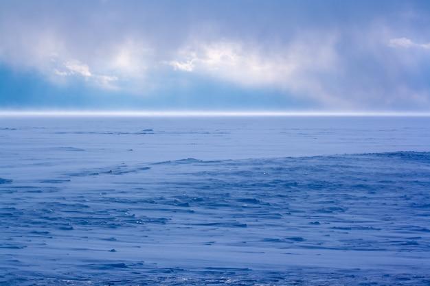 Zimą silna burza śnieżna nad jeziorem bajkał. nie widać lodu. dużo śniegu. słońce prześwieca przez chmury. silny wiatr zamiata śnieg. niebieski kolor śniegu. poziomy.