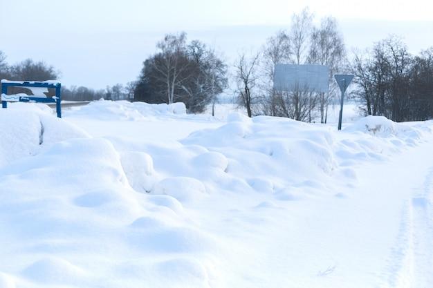 Zima słabo oczyszczona droga. droga na wsi usiana śniegiem. zimowy pejzaż z zaspami