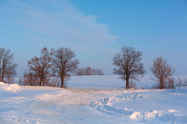 Zima słabo oczyszczona droga. droga na wsi usiana śniegiem.