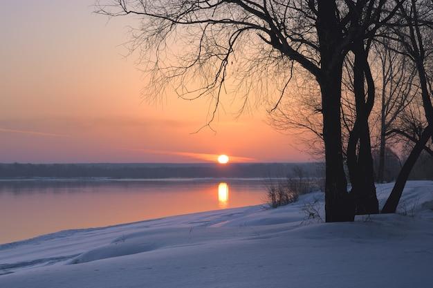 Zimą słońce wzeszło nad horyzontem brzeg rzeki ob pokryty jest niebieskimi zaspami