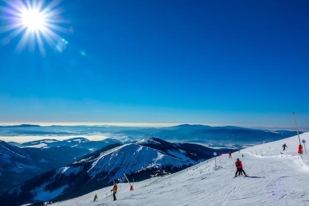 Zima słowacja. ośrodek narciarski jasna. panoramiczny widok ze szczytu ośnieżonych gór i stoku narciarskiego z narciarzami