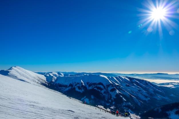 Zima słowacja. ośrodek narciarski jasna. widok ze szczytu na ośnieżone szczyty gór i stok narciarski z narciarzami