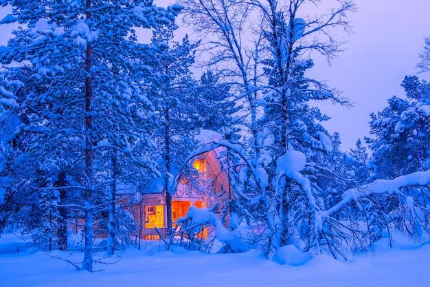 Zima w fińskiej laponii. światło samotnej chaty w gęstym lesie wieczorem. dużo śniegu