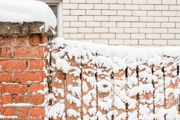 Zima we wsi. drewniany zamrożony płot. śnieg i sople są wszędzie.