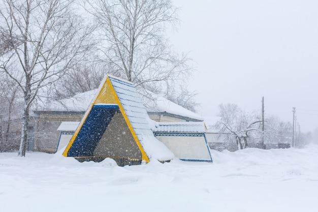 Zima, wiejskie ulice pokryte są śniegiem. zamieć śnieżna