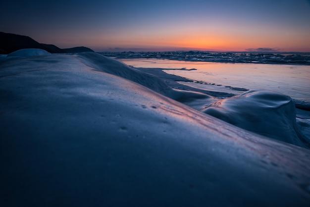 Zimą zamarznięte jezioro z przezroczystymi blokami lodu o wschodzie słońca