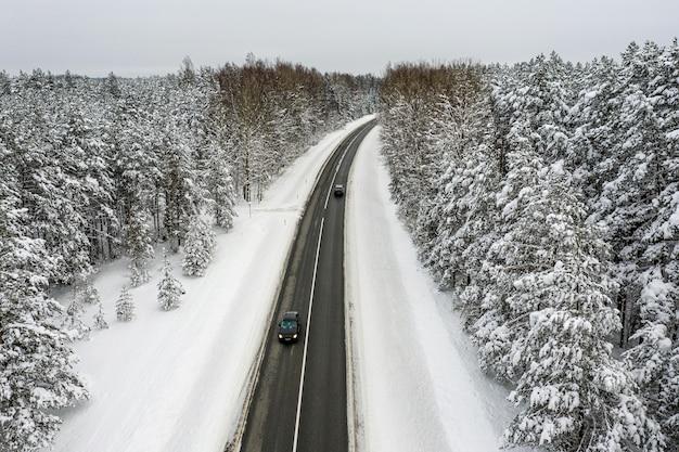 Zimą zaśnieżony las iglasty i droga z lotu ptaka