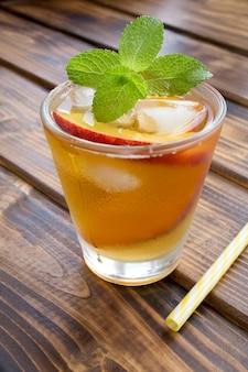 Zimna herbata z brzoskwiniami w szklance na brązowym tle drewnianych. lokalizacja w pionie.