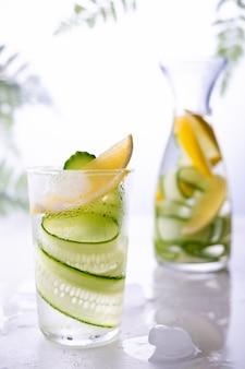 Zimna i orzeźwiająca naparowana woda detoksykacyjna z cytryną i ogórkiem w szklance. domowa lemoniada o smaku