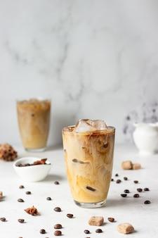 Zimna kawa z przyprawami i mlekiem na jasnoszarej powierzchni