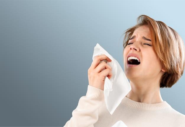Zimna kobieta trzymająca chusteczkę dmuchającą nos