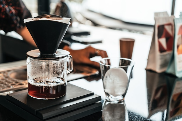 Zimna kroplówka arabica czarna kawa w szklance z lodową kulką