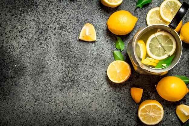 Zimna lemoniada w dzbanku z plasterkami cytryny i zielonych liści.