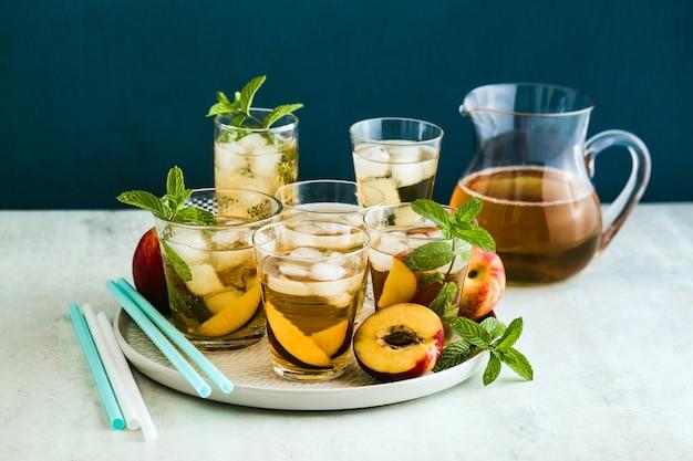 Zimna letnia herbata z brzoskwinią i miętą w szklankach na stole