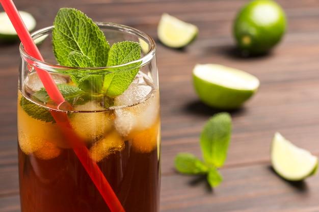 Zimna letnia herbata z lodem i miętą. na stole są liście limonki i mięty.