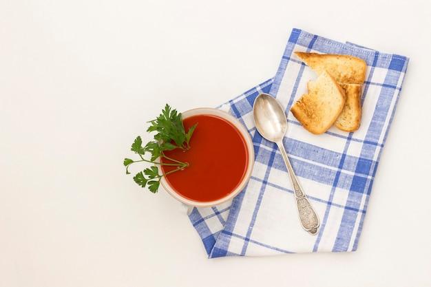 Zimna letnia zupa pomidorowa. serwetka w niebieską kratkę. białe tło. jest miejsce na tekst