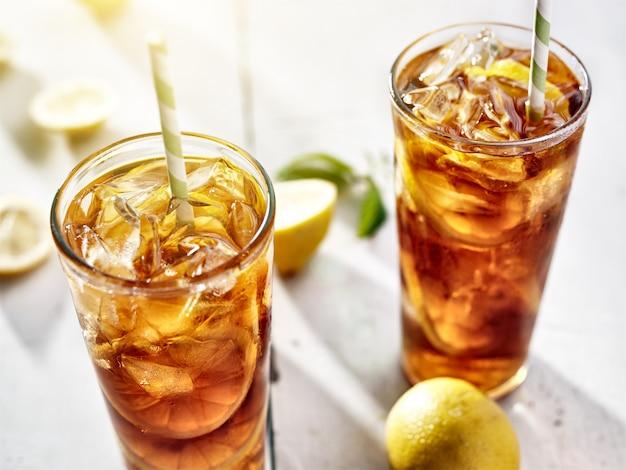 Zimna mrożona herbata ze słomkami i plasterkami cytryny w letnim słońcu.