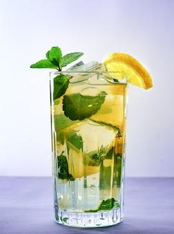 Zimna orzeźwiająca letnia lemoniada w szklance na szarym tle