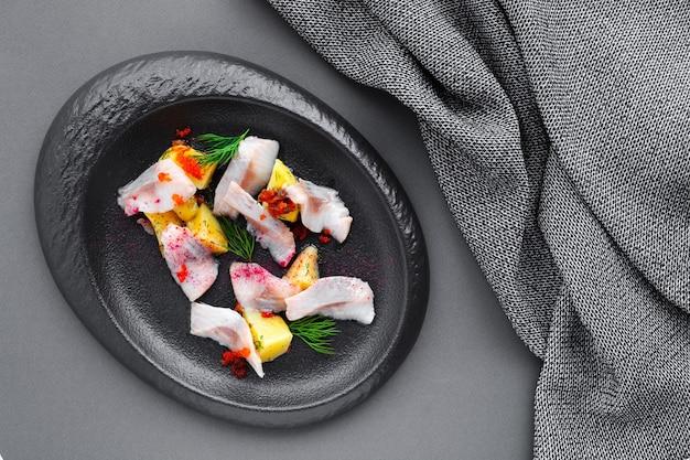 Zimna przekąska solony śledź z gotowanymi ziemniakami na czarnym talerzu, serwetka tekstylna, zbliżenie, widok z góry, układanie na płasko, miejsce na tekst, poziome