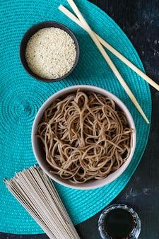Zimna soba (makaron gryczany) z sosem i sezamem. japońskie jedzenie. tradycyjna kuchnia azjatycka - makaron z mąki gryczanej. widok z góry, leżał płasko. transparent