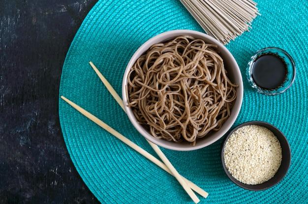 Zimna soba (makaron gryczany) z sosem i sezamem. japońskie jedzenie. tradycyjna kuchnia azjatycka - makaron z mąki gryczanej. widok z góry, leżał płasko.